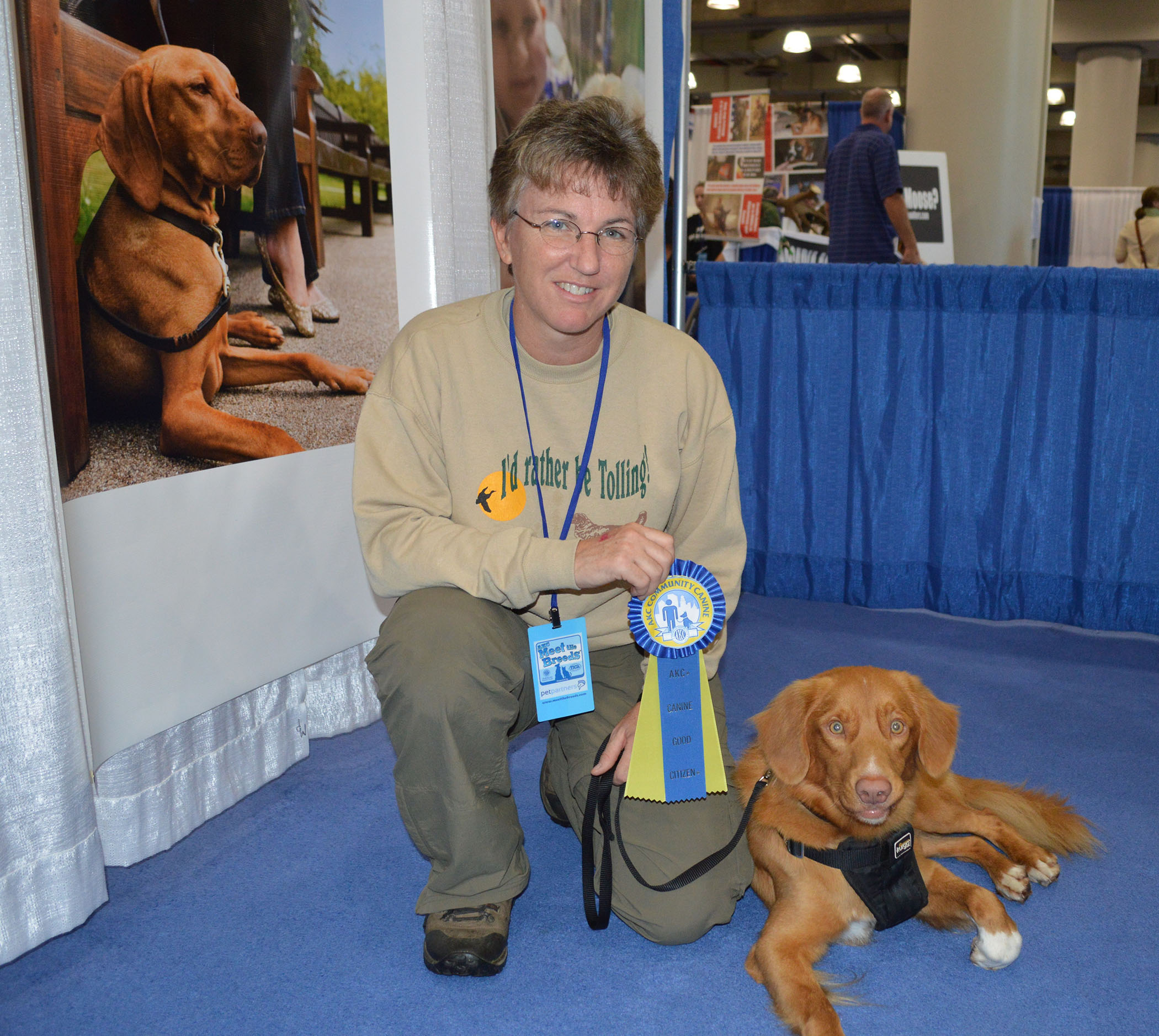 owner and male toller with ribbon for canine good citizen advanced